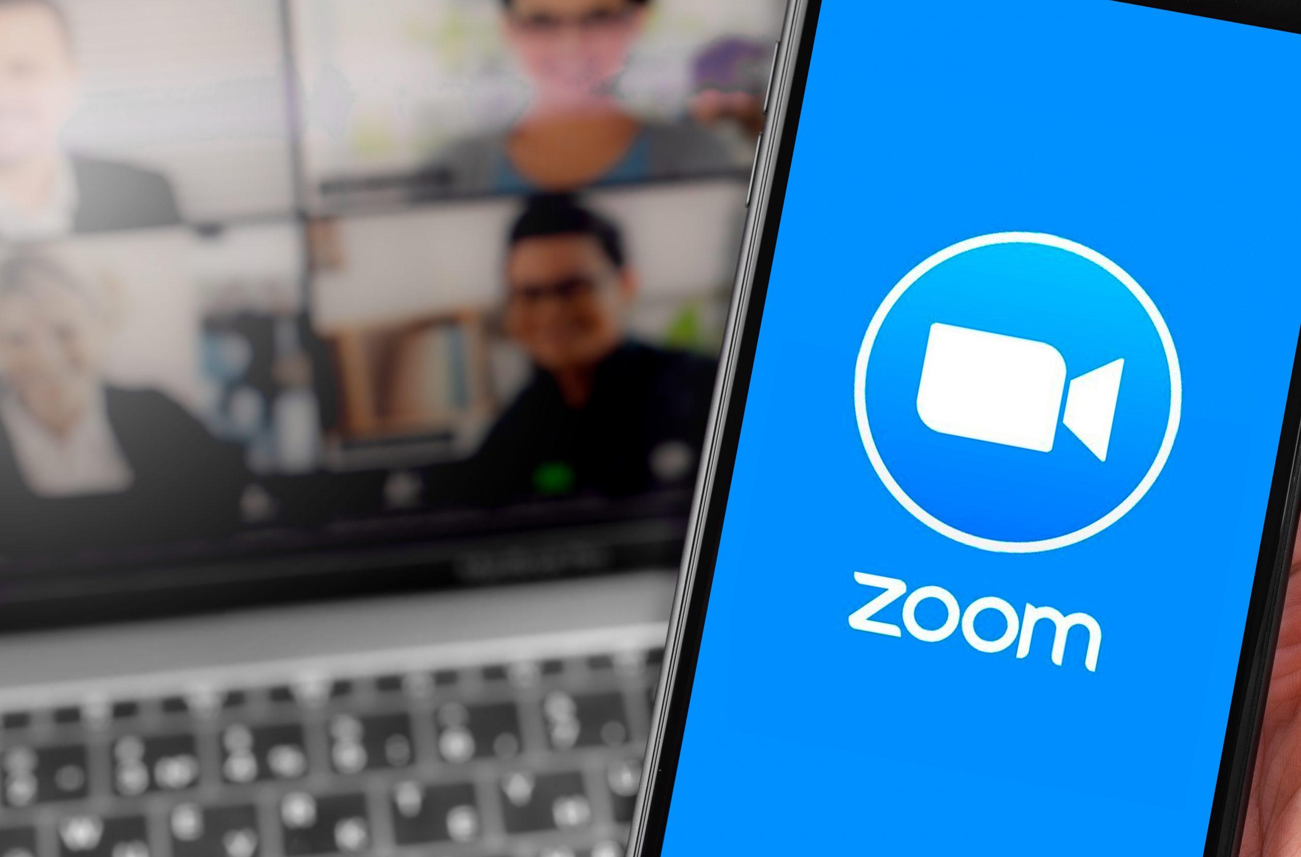 Zoom Logo und Videokonferenz auf einem Computer