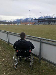 Niklas Funke von hinten beim Groundhopping im Rollstuhl aufgenommen. Er blickt auf ein Stadion und eine Berglandschaft im Hintergrund.