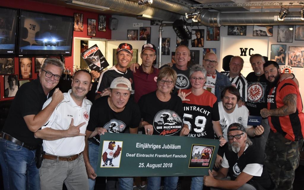 """Auf dem Bild sieht man 14 Mitglieder, die in die Kamera schauen und lächeln. Zwei halten das Banner """"Einjähriges Jubiläum Deaf Eintracht Frankfurt Fanclub 25.August 2018"""" fest."""